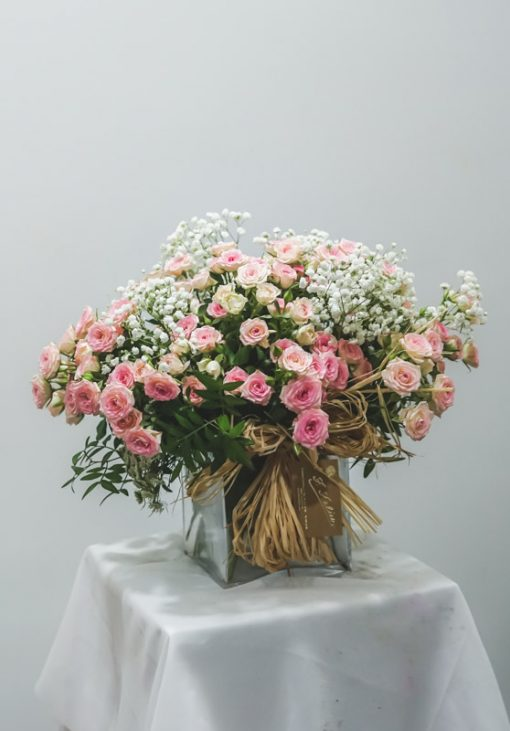 Imagen de recipiente de cristal con rosas de pitiminí en rosa y paniculata