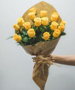 Ramo de rosas amarillas envuelto en papel